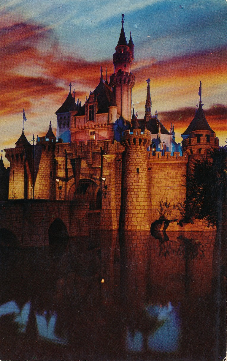 Sleeping Beauty's Castle at sunset, and it blazes pale orange and reds with a pink and blue sky behind it.