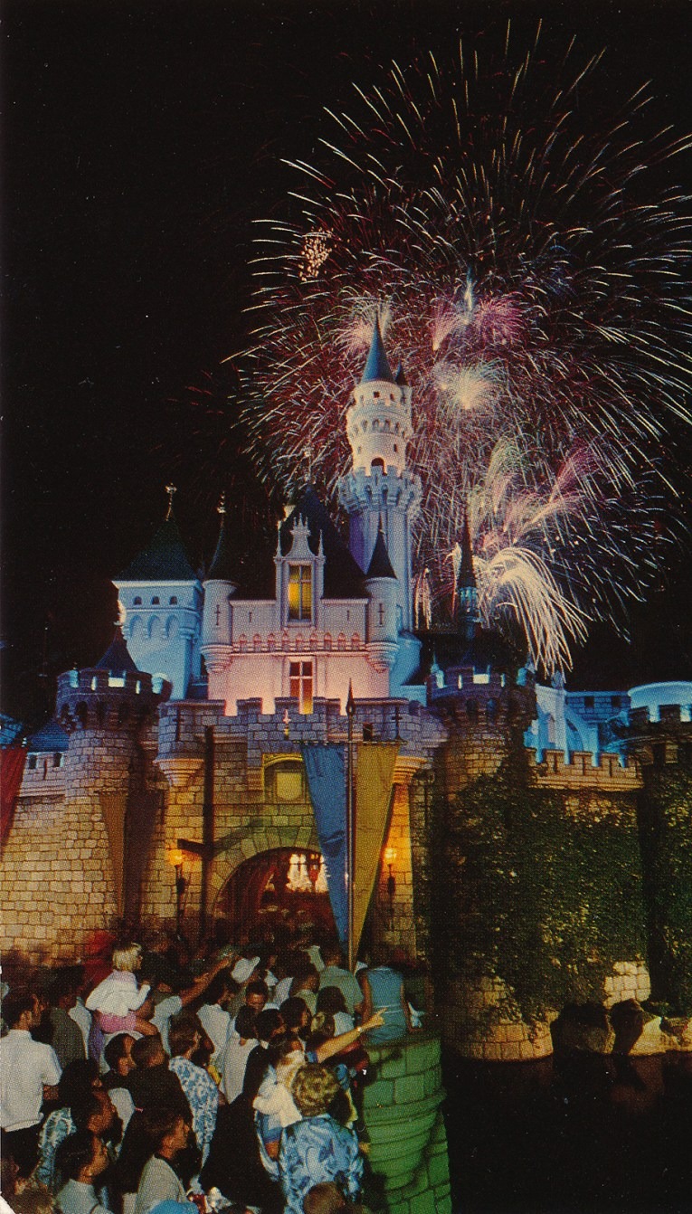 Sleepy Beauty's Castle with fireworks going off behind it. People line the drawbridge for a look.