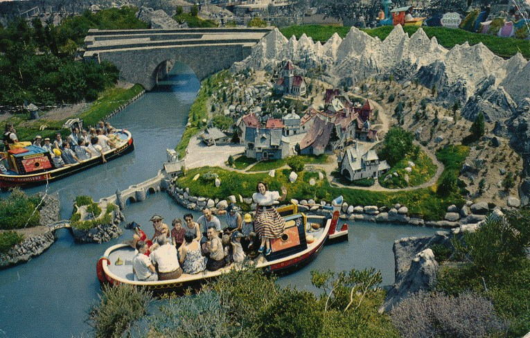 One of the boats from Storybookland, as it glides past miniatures of the homes from the various animated features.