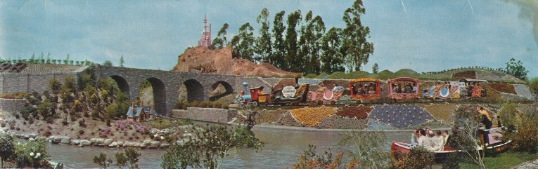 Casey Jr. travels along its tracks with colorful plants nearby. A miniature version of Cinderella's castle stands tall in the distance.