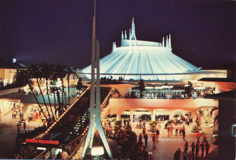 Towering Space Mountain, a white building with spires atop it. A massive escalator takes guests upwards toward the building.