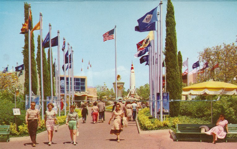 Entrance to Tomorrowland, flags from all over the world flank a pathway toward a clock with a moon and sun on top, and a tall rocket looms in the background.