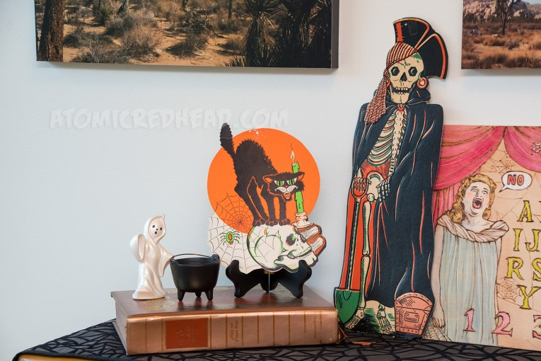 Close-up of the pirate skeleton, and cat sitting top a skull.