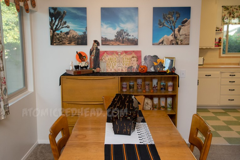 Down the dining room table, toward the secretary. The table features a black, orange, and silver stripe runner. In the middle a cardboard haunted house.