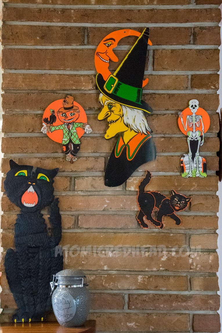 A black cat, scarecrow, witch, smaller black cat, and skeleton.
