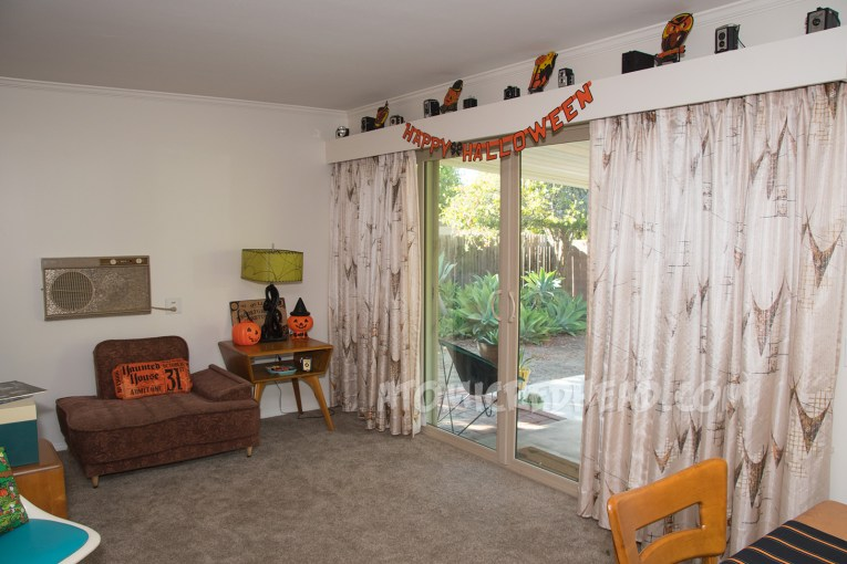 """To the right curtains hang in front of a sliding glass door, above the sliding glass door a banner reads """"Happy Halloween"""" in orange, edged in black. Above it are vintage cameras, along with cardboard Halloween decorations of a witch, owl, cat, and pumpkin. On the left a 50s chair sits next to a table, a pillow that looks like a ticket stub for a Haunted House sits on it. On the table a plastic jackolantern trick-or-treat bucket and a pumpkin with a witch hat on it."""