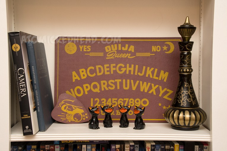 """A maroon spirit board reading """"Ouija Queen"""" and a series of ceramic black cats sit."""
