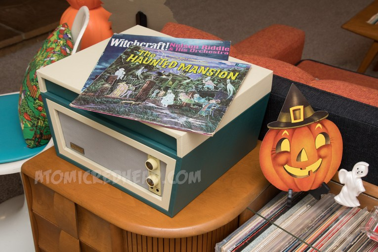 A cream and teal record player with a Disney Haunted Mansion record atop it. Next to the record player a cardboard jackolantern wearing a witch hat and a ceramic ghost sits next to it.