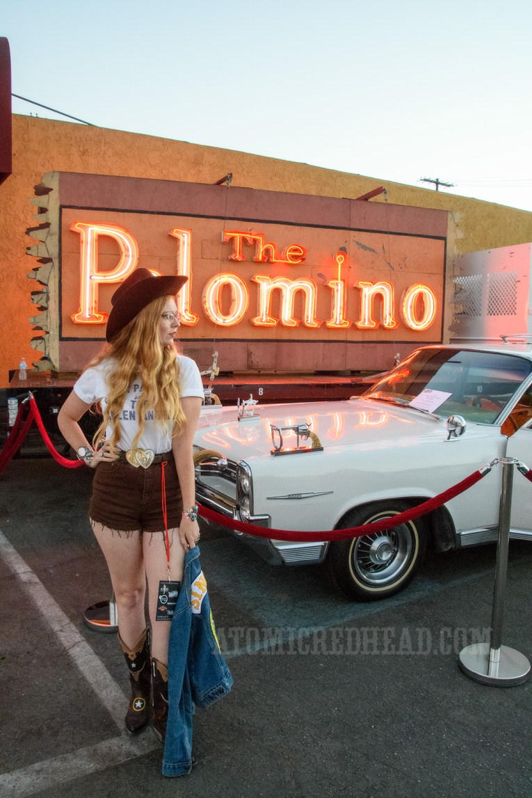 "Myself standing in front of one of Nudie's cars, which features bull horns on the grill, a guns atop the front fenders. In the background sits the red neon glowing sign of The Palomino. Myself standing in front of the car wearing a dark brown cowboy hat, a white t-shirt reading ""Gram Parsons and the Fallen Angels"", dark brown cut off shirts, and holding a jean jacket."