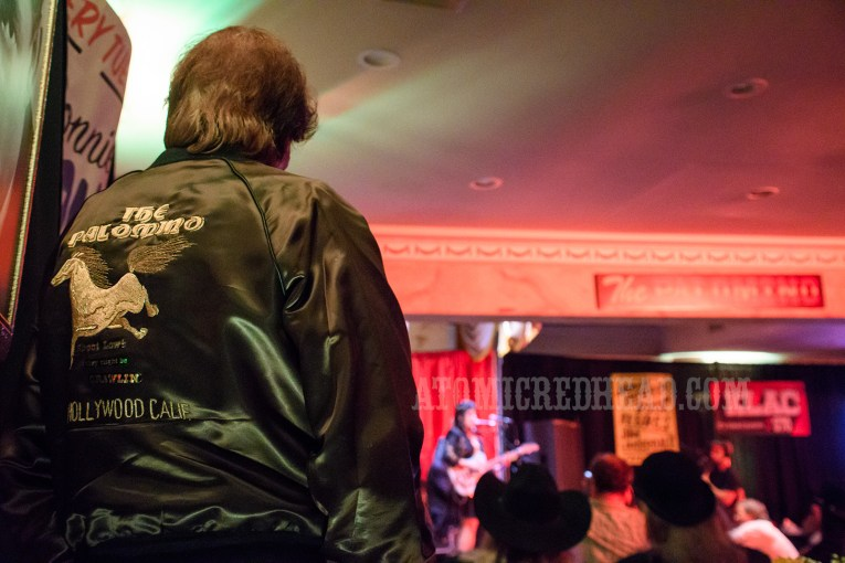 "Ronnie Mack leans against the wall, facing the stage, his back to the camera, wearing a black satin jacket reading ""The Palomino"" and features an embroidered horse."