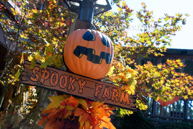 "A cartoon pumpkin with a painted on jack-o-lantern face hangs on a post, a sign reading ""Spooky Farm"" hangs below."