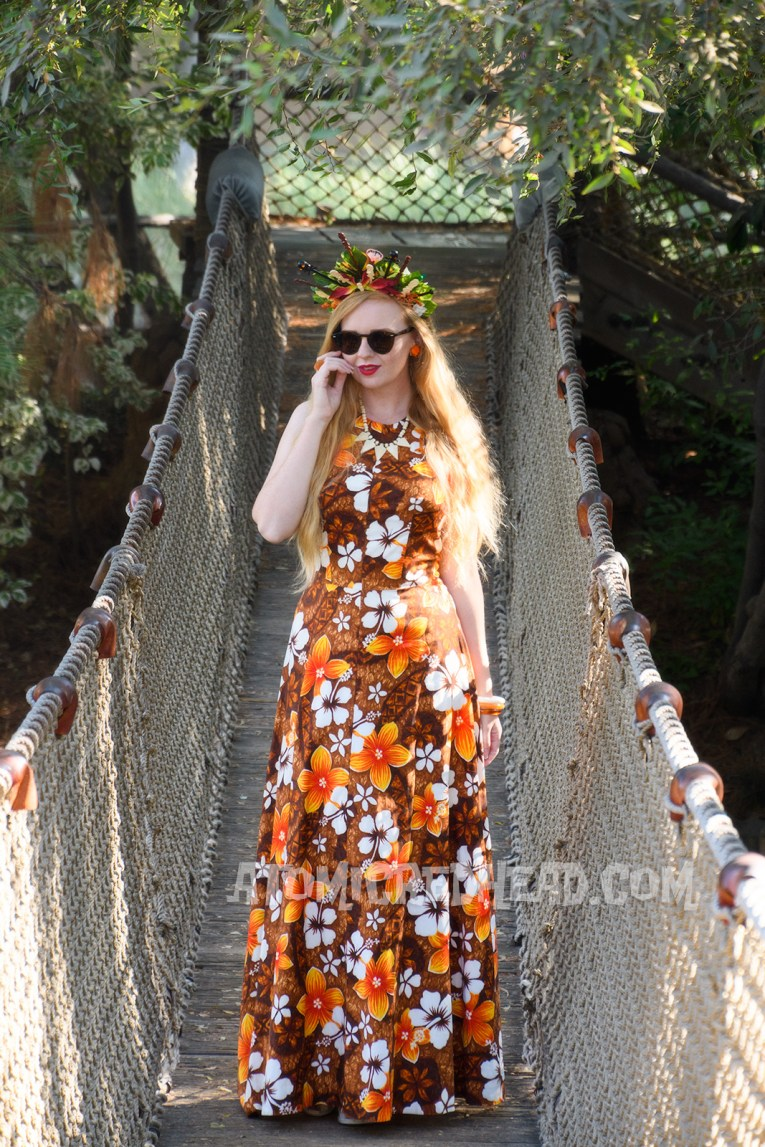 Myself, standing on a bridge, wearing a brown, orange, and white floral maxi dress, and a crown made of orange and yellow flowers and swizzle sticks from Trader Sam's, featuring tiny tikis.
