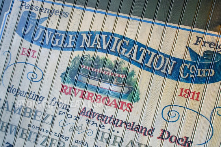 "Mural of the Jungle Cruise, featuring an image of one of the boats gliding through the water. Reads ""Jungle Navigation Company Riverboats. Departing from the Adventureland Dock"""