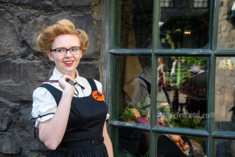 Wondering peeking into the shop windows of Hogsmeade, wearing a white blouse under a black dress. A brooch of a witch on a broom worn on my left.