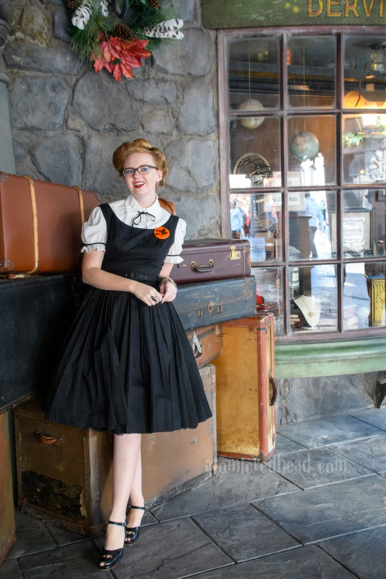 Packages await being delivered by Owl at the Owl Post, leaning against the pile A stack of cauldrons marks the entrance to the Magical Neep, a shop in Hogsmeade, wearing a white blouse under a black dress. A brooch of a witch on a broom worn on my left.