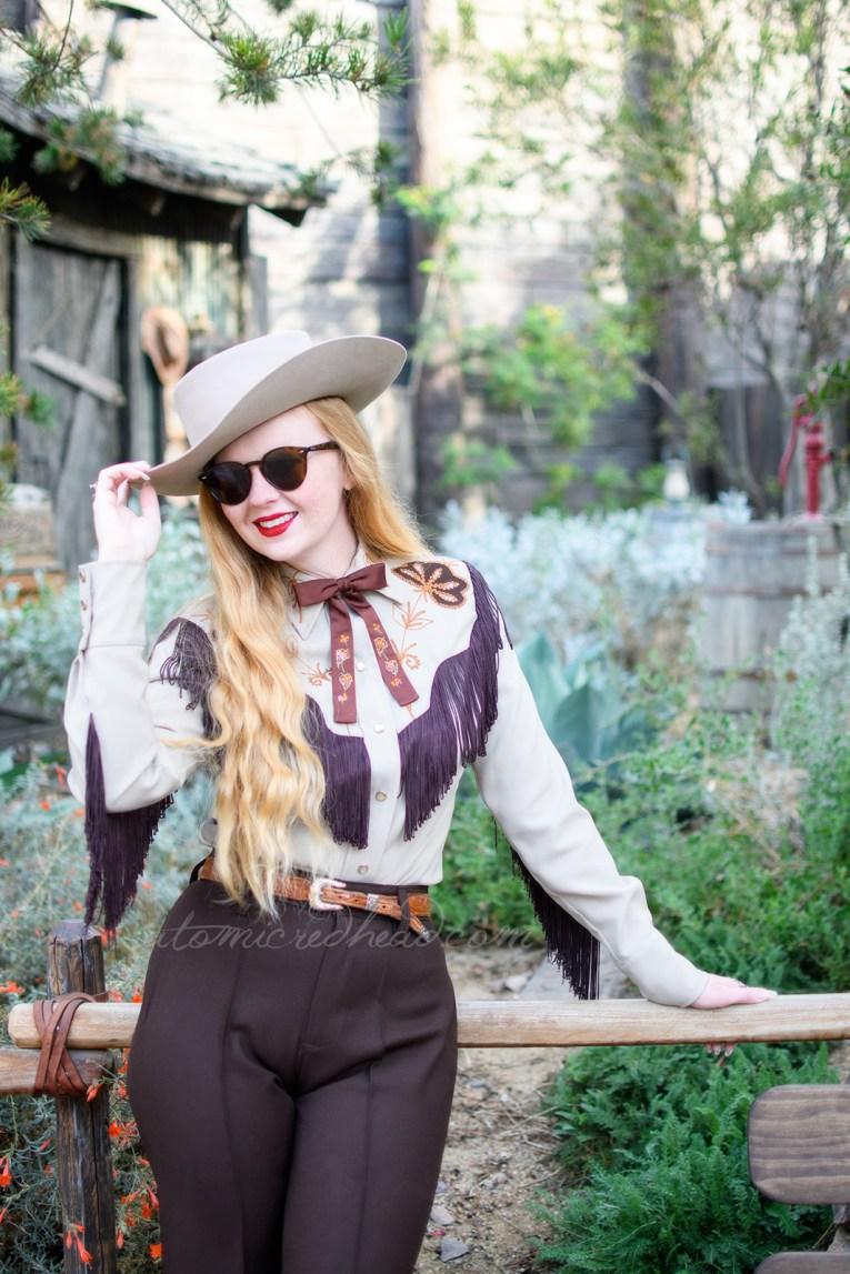 Myself, standing in front of a little shack surrounded by cacti and succulents, wearing a tan cowboy hat, a tan western wear shirt with dark brown fringe, and embroidered flowers, a dark brown string tie with painted flowers, and dark brown western pants with orange flowers embroidered near the bottom.