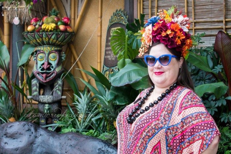 Kaitlyn, standing in the Enchanted Tiki Room courtyard, a large tiki stands in background among large green leaves. Kaitlyn wears a large flower crown made up of maroon, orange, and blue flowers, her dress is a patterned gown of red, orange, blue, and white.