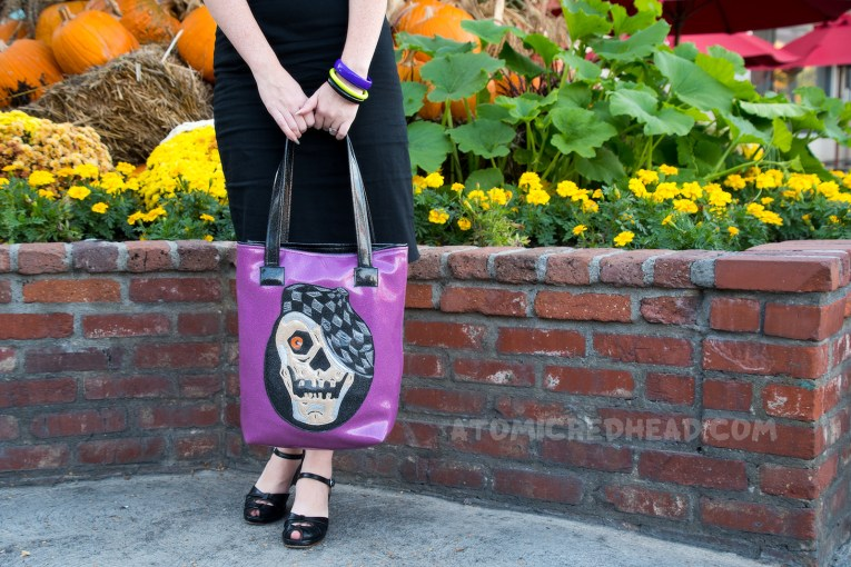 Close-up of my purse, purple glitter vinyl, and a skull with a checkerboard cap.