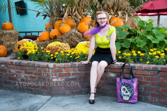Myself, sitting in front of a planter of orange and yellow flowers, and pumpkins, wearing a lime green peasant top, black pencil skirt, and purple scarf, and a purple bag with a skull wearing a cap.