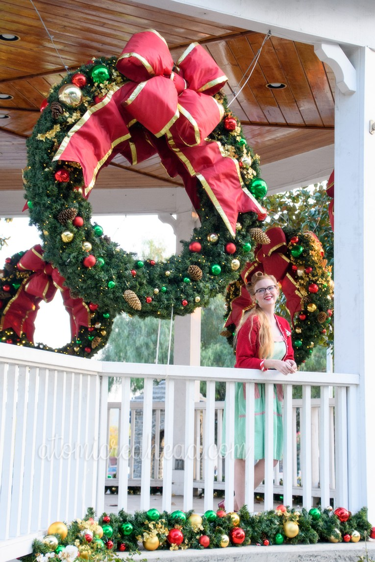 Leaning on the railing of the bandstand, looking out, wearing a mint green dress with red and white stripe pockets, a red sweater, a Christmas tree brooch, white purse, and red shoes. A large Christmas wreath hangs in the background.