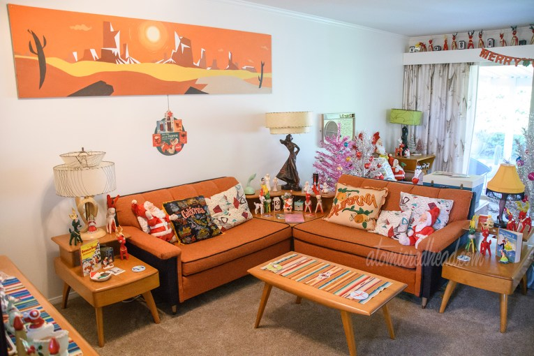 An overall view of our living room. A painting of a desert scape hangs on the wall above an orange and black couch. Small stuffed Santas sit on the couch.