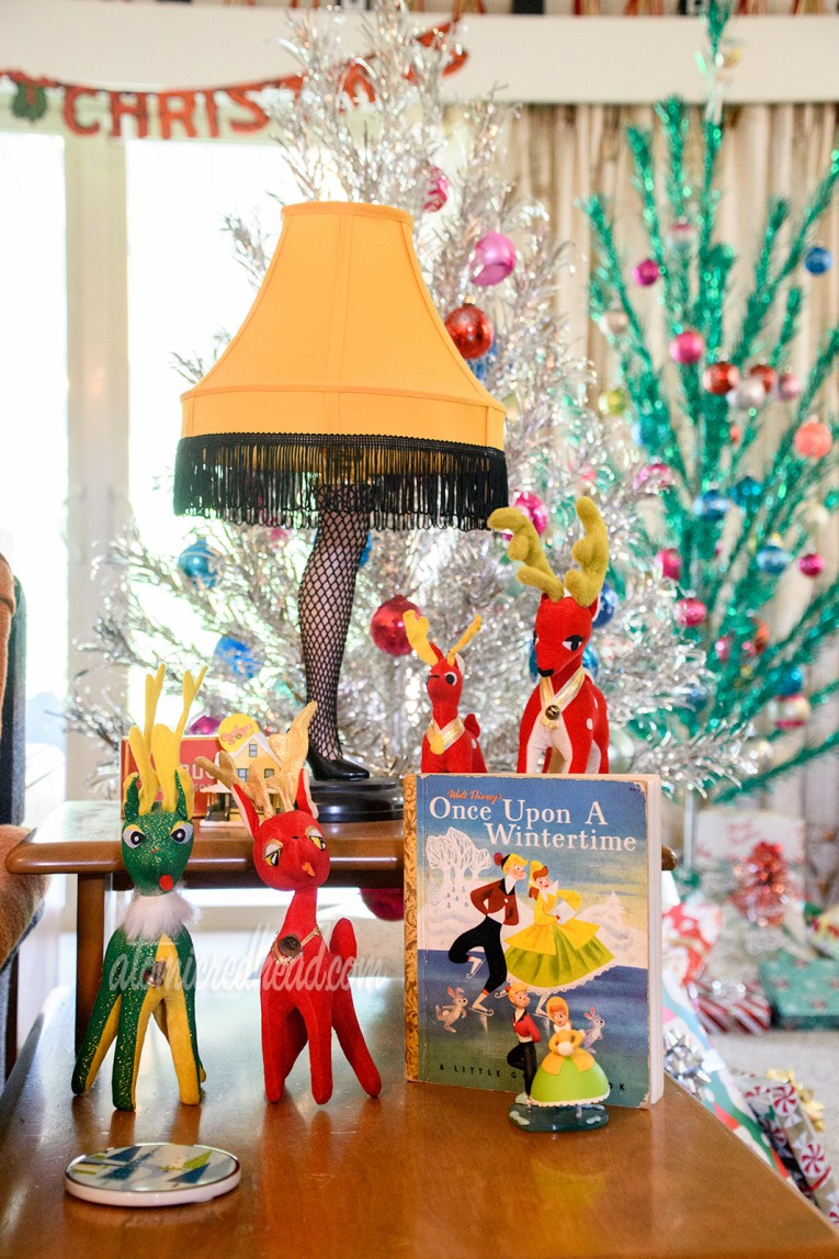 """The iconic Leg Lamp from A Christmas Story sits on an end table, with various small, stuffed reindeer, and a book of """"Once Upon a Wintertime"""" which features a boy and girl ice skating."""