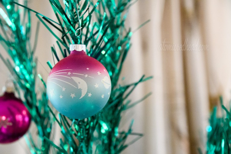 Close up of a pink, white, and blue colored glass ornament featuring a moon and shooting star hanging from a green aluminum tree.