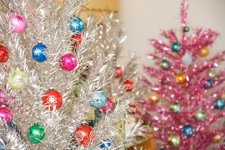 In the foreground a silver aluminum tree features multi-colored glass ball ornaments with stars, moons, and planets on them. In the background a pink aluminum tree with similar ornaments.