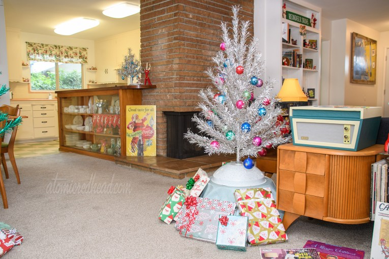 A small silver aluminum tree stands with various colored ornaments featuring moons, stars, and planets. In the background a fireplace, and further back the kitchen.