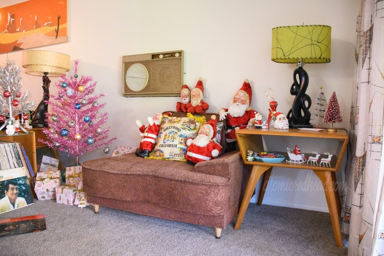 A mauve colored chair holds a variety of vintage stuffed Santas.