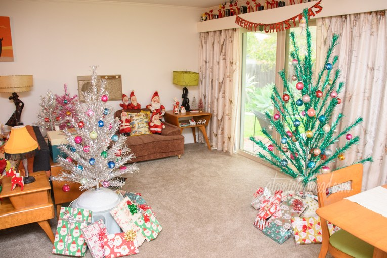 An overall shot of part of our living room featuring the six foot tall green aluminum tree on the right, a four foot tall silver aluminum tree on the right. A mauve colored chair sits against the wall in the back with small, vintage stuffed Santas.