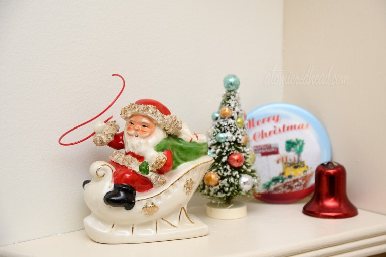 A small ceramic santa carries a whip as he rides in his sleigh.