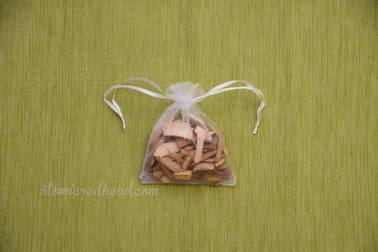 A small organza sachet bag is filled with wood chips.