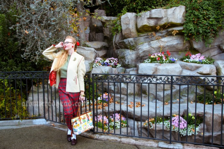 Myself standing in front of some grey stones with some flowers tucked between them. I'm wearing a cream jacket with some embroidery, a green sweater, and red and grey plaid pants. A D shaped brooch with holly on it is pinned to the jacket.