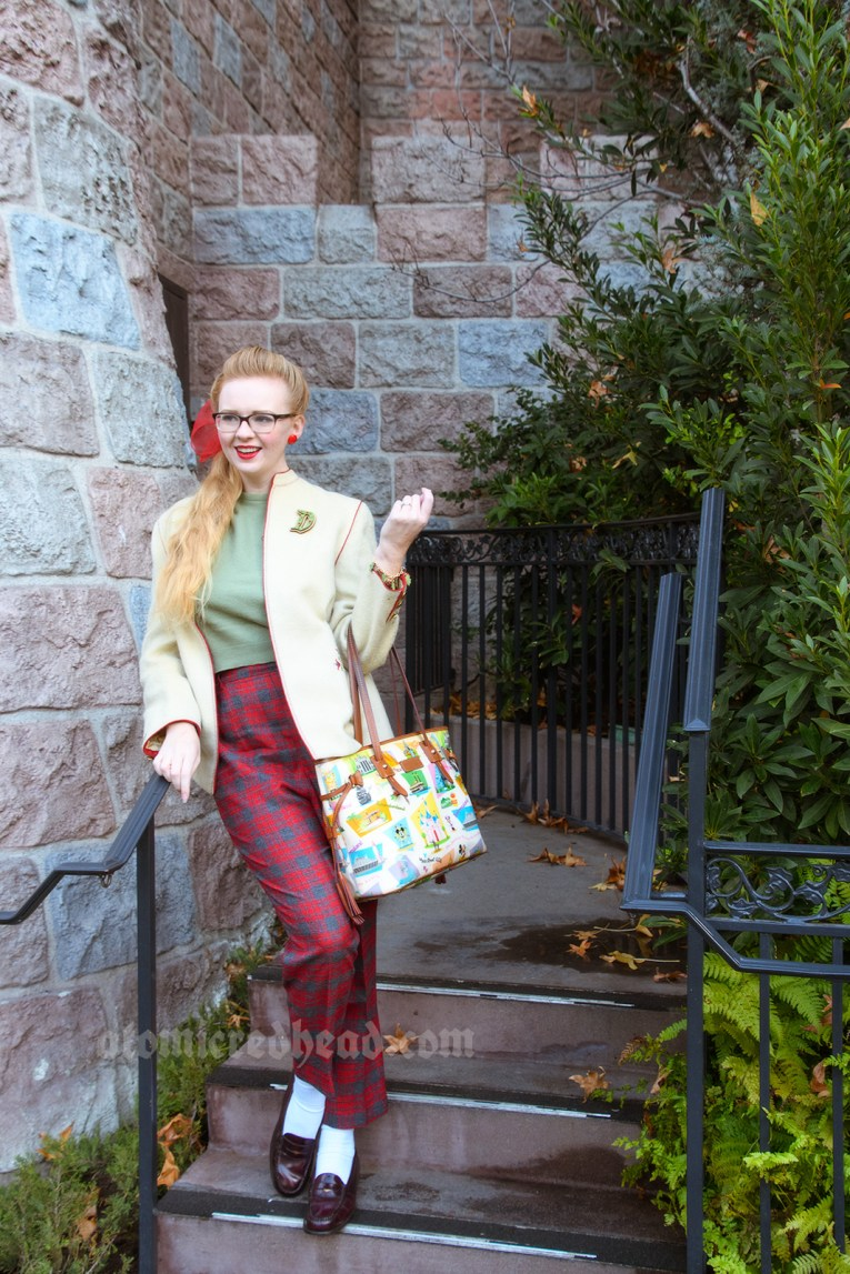 Myself, standing near Sleeping Beauty Castle wearing a cream jacket with green and red embroidery, a green sweater, and red and grey plaid pants. On the jacket a D shaped brooch with holly on it.