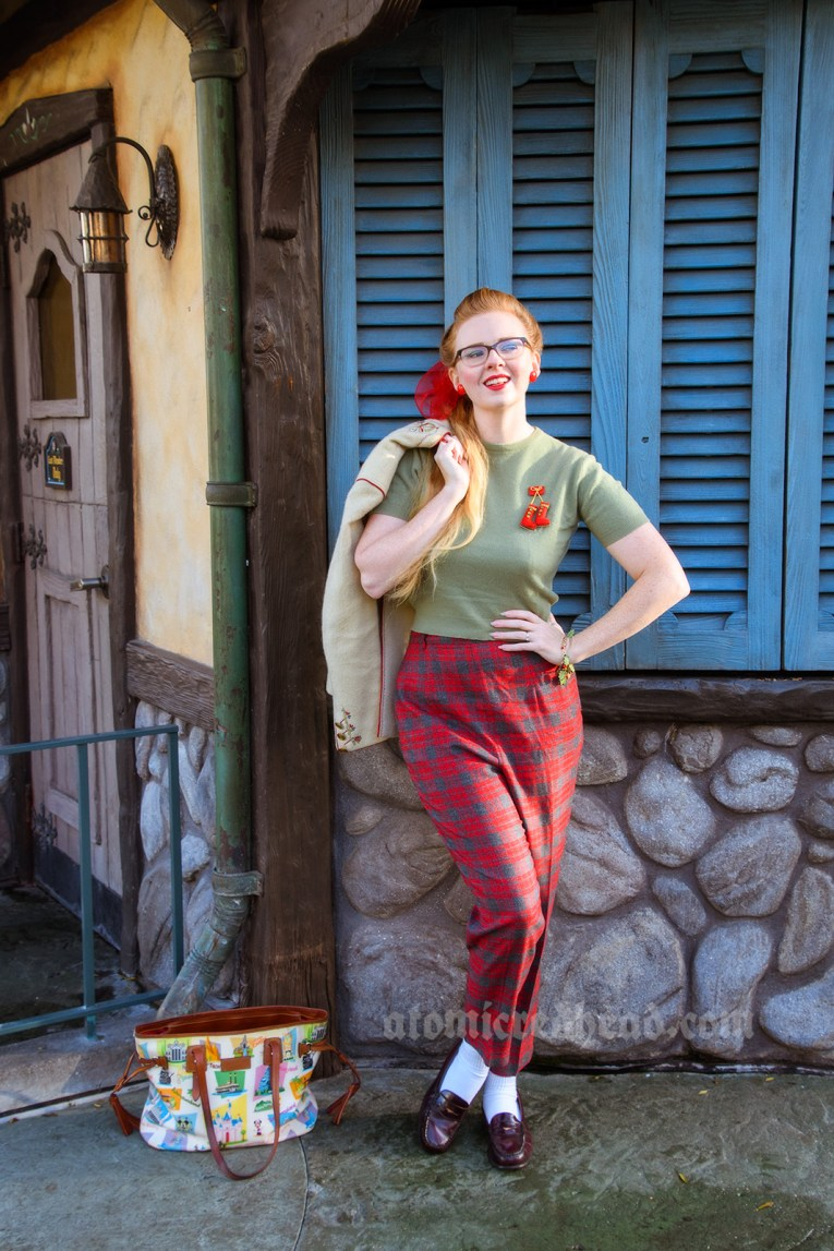 Myself standing near a blue shuttered building inspired by the Swiss Alps, wearing a green sweater and red and grey plaid pants. My hair is in a ponytail, tied with a red scarf. A red brooch featuring small ice skates is pinned to my sweater.