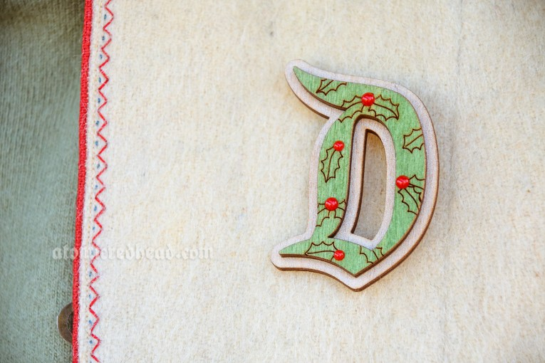 Detail of the D shaped brooch, which is laser cut wood with a holly design, and small raised red berries.