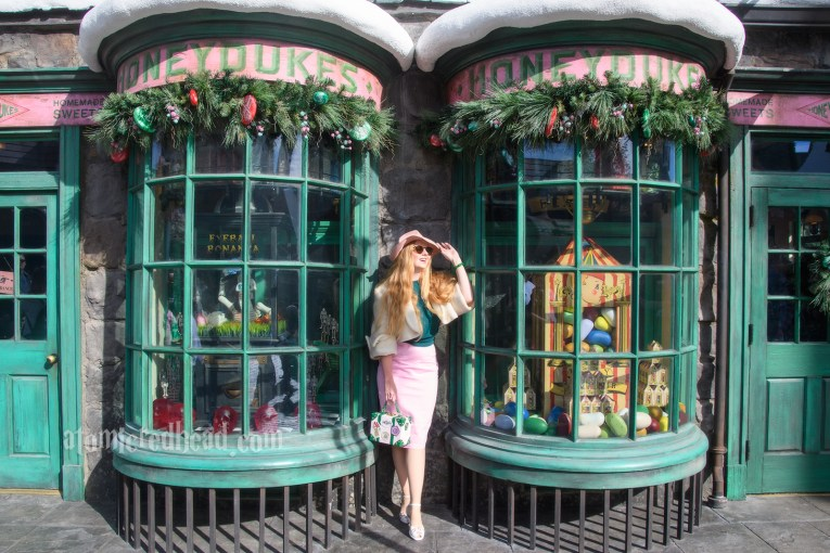 Myself standing outside of Honeydukes. Windows filled with candy. I'm wearing a pink fedora, white bolero jacket, forest green sweater, and a pink pencil skirt, white and pink shoes, and a pink, white, and green purse featuring icons of Honeydukes.