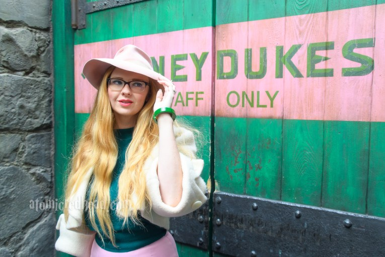 """Myself standing in front of a large green door with a large pink stripe across it which reads """"Honeydukes Staff Only."""" I'm wearing a pink fedora, white bolero jacket, green sweater, pink skirt, and carrying a pink, white, and green purse featuring Honeydukes treats."""