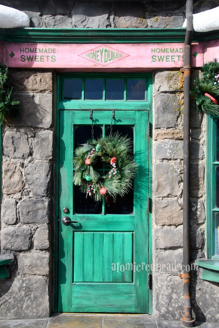 A forest green door stands tall between grey stones. On the door a wreath of evergreen branches, filled with candy.