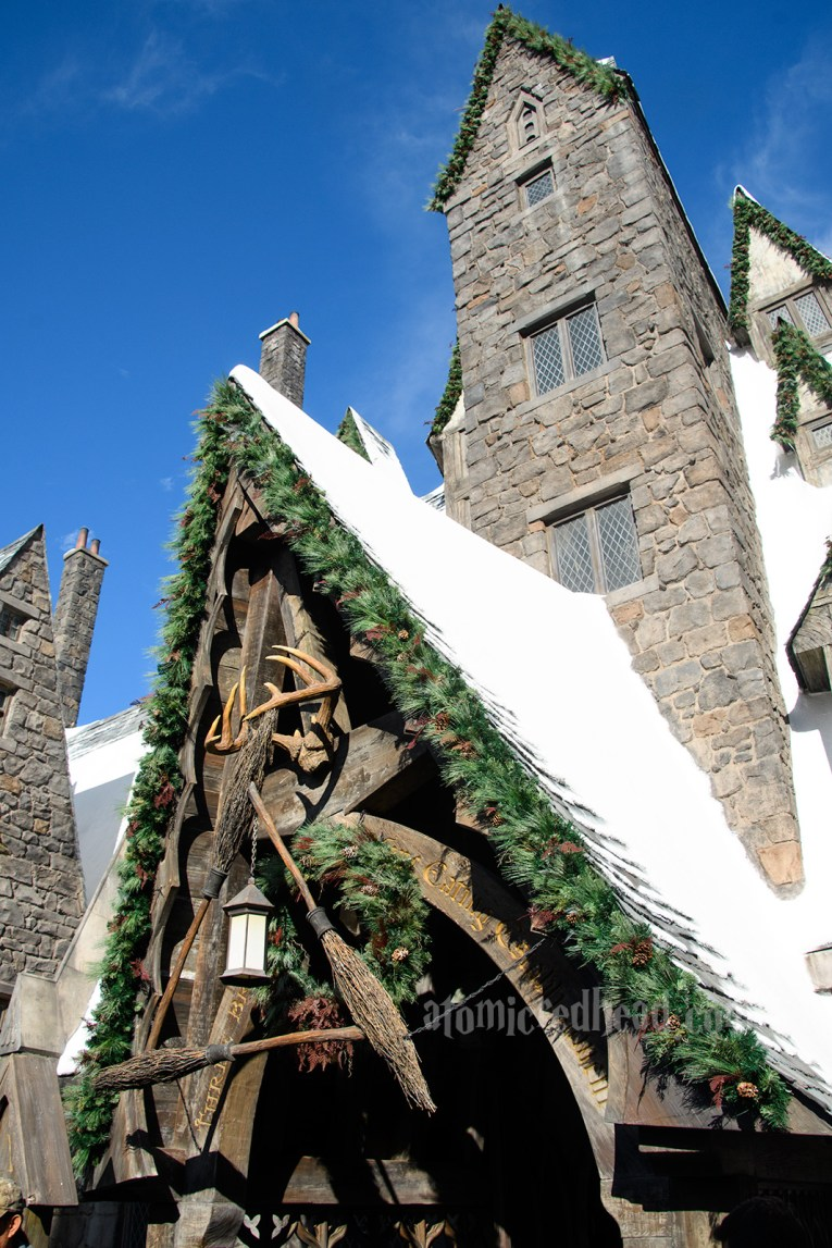 The Three Broomsticks roof is toped with snow, and the eves have green garlands on them.