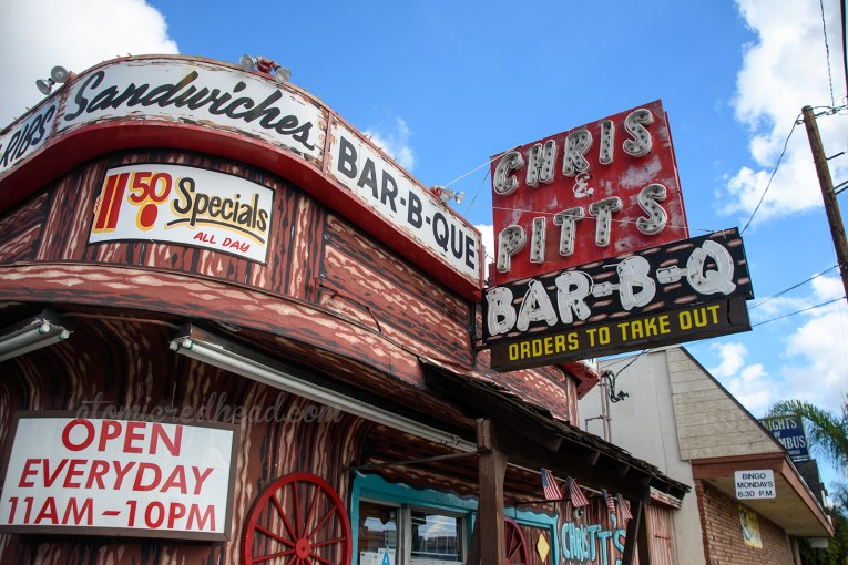 "Chris and Pitt's resides in a building painted to resemble a log cabin, and features signs along its top reading ""Sandwiches, Bar-B-Q"" and a large red and black neon sign reading ""Chris & Pitt's Bar-B-Q"""