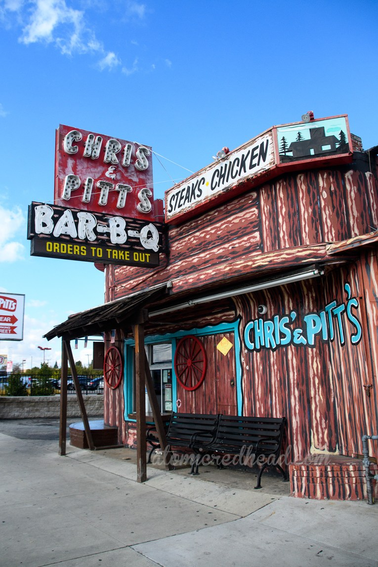 "Chris and Pitt's resides in a building painted to resemble a log cabin, and features signs along its top reading ""Sandwiches, Bar-B-Q"" and a large red and black neon sign reading ""Chris & Pitt's Bar-B-Q"" Along the side in turquoise painted letters reads ""Chris & Pitt's"""