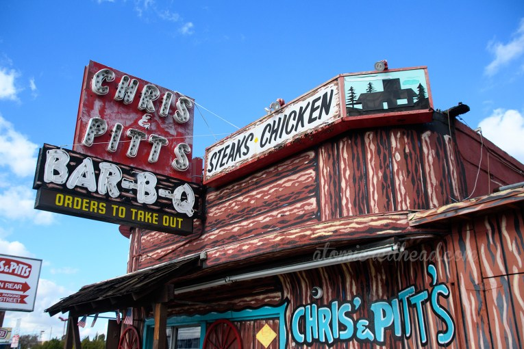 """Chris and Pitt's resides in a building painted to resemble a log cabin, and features signs along its top reading """"Sandwiches, Bar-B-Q"""" and a large red and black neon sign reading """"Chris & Pitt's Bar-B-Q"""" Along the side in turquoise painted letters reads """"Chris & Pitt's"""""""