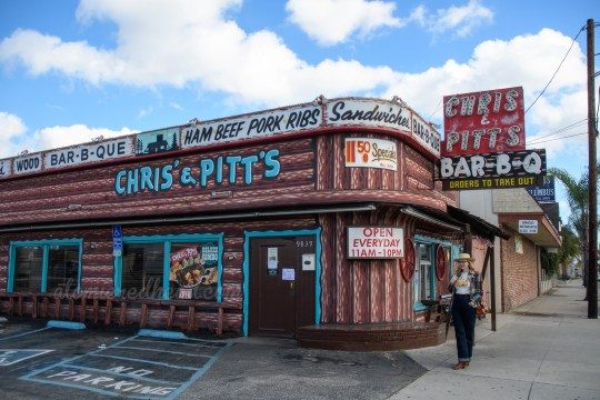 "Chris and Pitt's resides in a building painted to resemble a log cabin, and features signs along its top reading ""Sandwiches, Bar-B-Q"" and a large red and black neon sign reading ""Chris & Pitt's Bar-B-Q"" Along the side in turquoise painted letters reads ""Chris & Pitt's"" I stand below the large sign in a pair of wide leg jeans, a t-shirt featuring a cowgirl pin-up who has been bucked off a horse, a blue and brown plaid jacket, and a cream cowboy hat."
