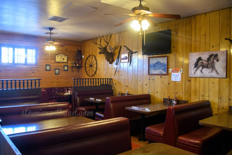Inside features wood paneling, maroon upholstered booths, and various western themed items hanging on the wall, such as a wagon wheel, a deer's head, and a painting of a horse.