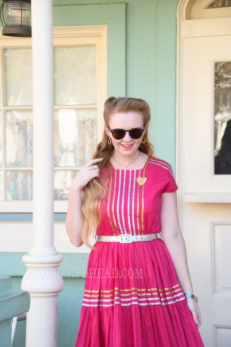 Myself standing in front of a pale green building with white trim, wearing a magenta dress with gold and silver ric-rac, a silver belt, and silver moccasins.