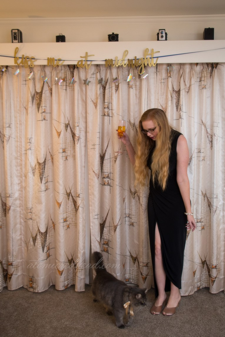 Myself in a long black dress with a high slit, standing in front of a mid-century modern curtain, looking down at my cat, who invades my photo space.