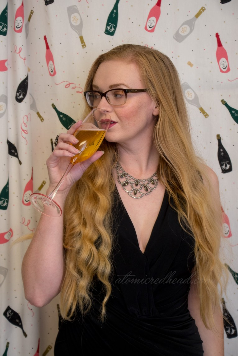 Myself standing in front of a curtain that has small champagne bottles and confetti, wearing a black dress, rhinestone necklace, and holding a champagne glass.