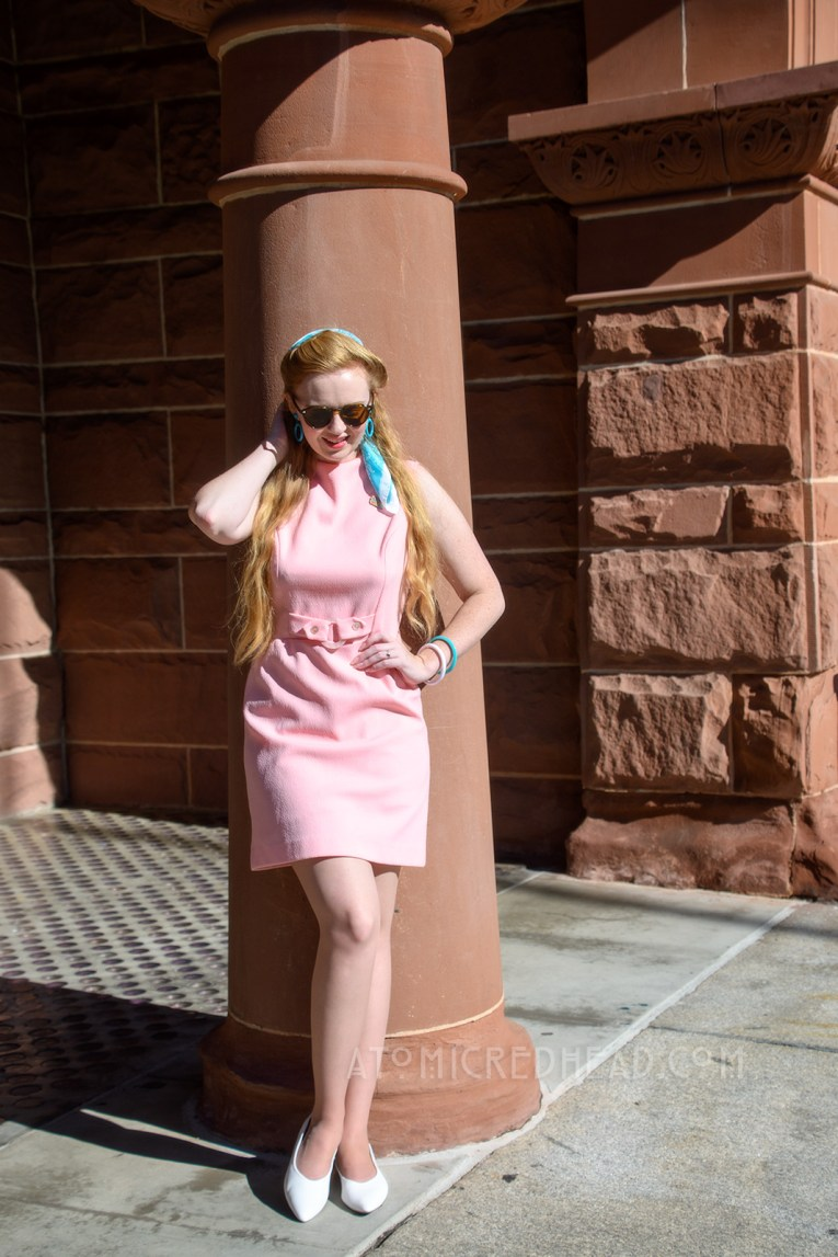 Myself standing in front of the red sandstone building, wearing a sleeveless pink mini dress with a blue scarf in my hair, and blue hoop earrings.